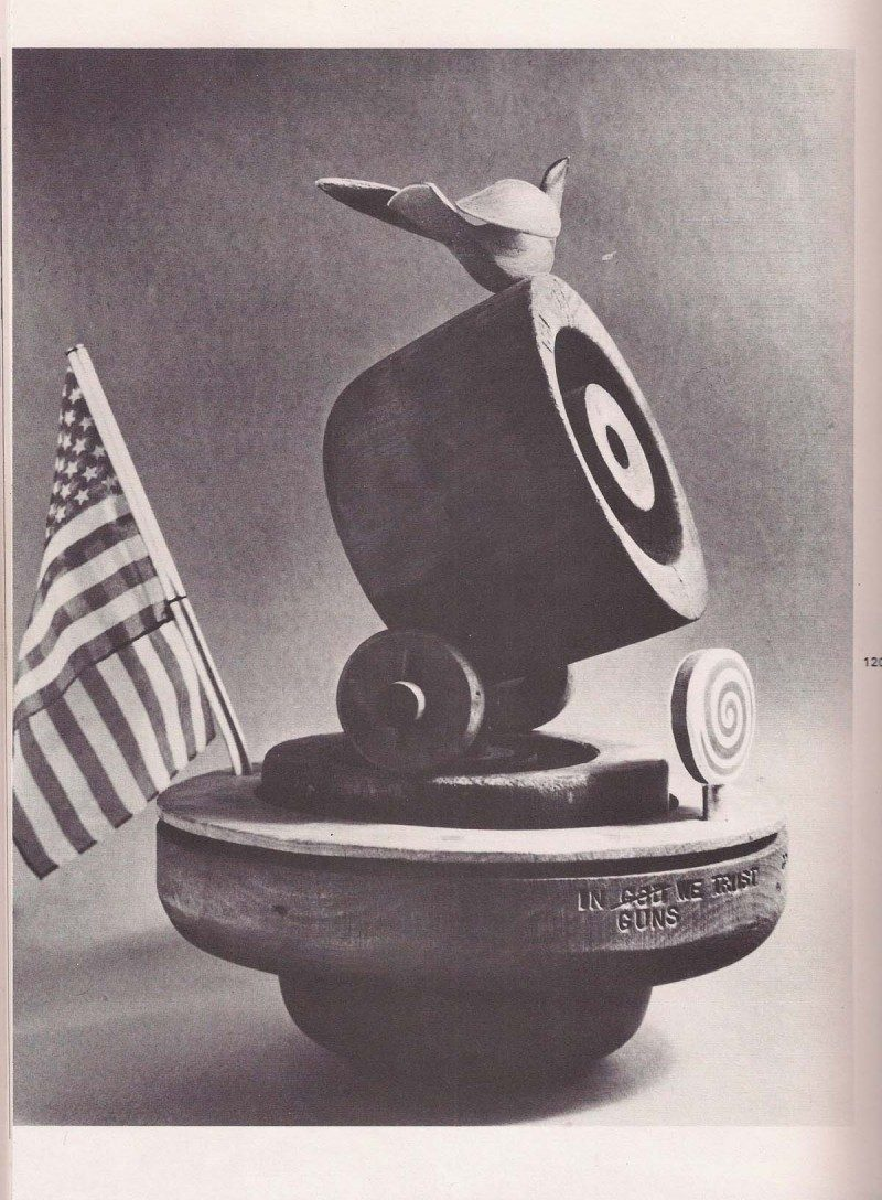Original Image from 1970's catalogue. 'In Guns We Trust' Rare Sculpture by Arthur Price, 'Good Ship Lollipop' aka 'In God (crossed out) Guns We Trust' 1972, Arthur 'Art' Price, Found Wood Antique Hat Forms & Bird Sculpture in Aluminum & Polychrome (made by the artist), Found American Dime 1960's, Spiral Wood Lollipop sculpture (made by the artist), 17 height x 10.5 width x 17 depth (with metal rod) inches. One of a kind sculpture. Titles & artist named stamped / see original photos from 1970's catalogue of the artist's artworks entitled 'Art Price. Happiness Is Where You Find It. Volume 2'. Price available upon request (current appraisal underway)
